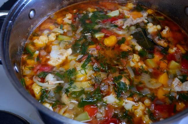 Посолите, приправьте суп и добавьте зелень
